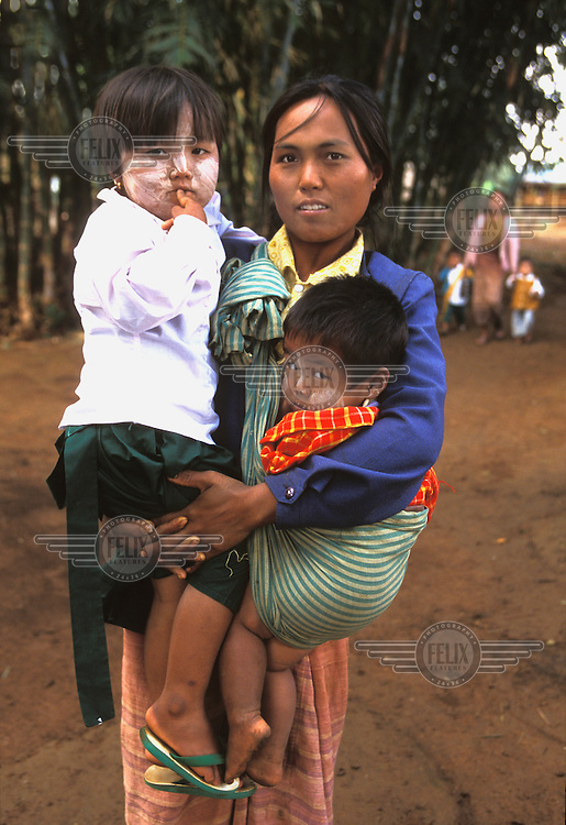 A mother brings two of her children to the Save the Children Fund's preschool at Oak Tha Kan village, Shan State. The children have 'tanaka' on their face, a natural sun-block made from the bark of sandalwood.