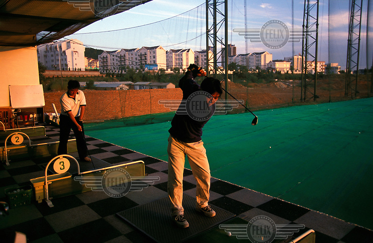 ©Mark Henley/Panos Pictures..China, Liaoning, Dalian Development Zone..New culture & sport as result of economic change. Man practising golf on Japanese -style driving range.