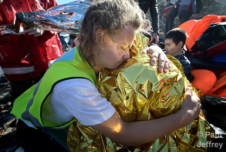 Tordar Tommervik (left), a volunteer from Norway, hugs a cold and frightened Afghan refugee boy on a beach near Molyvos, on the Greek island of Lesbos, on November 2, 2015. The boy was on a boat full of refugees that traveled to Lesbos from Turkey, provided by Turkish traffickers to whom the refugees paid huge sums to arrive in Greece. Tommervik is one of hundreds of volunteers on the island who receive the refugees and provide them with warm clothing and medical care before they continue their journey toward western Europe.