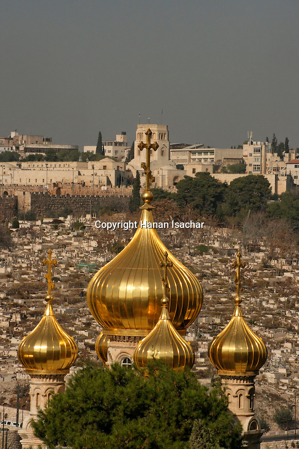 Jerusalem, Israel, The golden onion domes of the Russian Orthodox Church of St. Mary Magdalene on the Mount of Olives, the Rockefeller Museum is in the background<br />