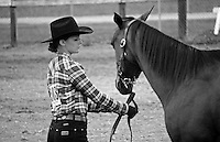 A young woman in a plaid shirt and cowboy hat performs with her horse at a horse show.