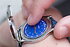 Vision impaired man feeling the hands of his specially adapted watch in order to tell the time,