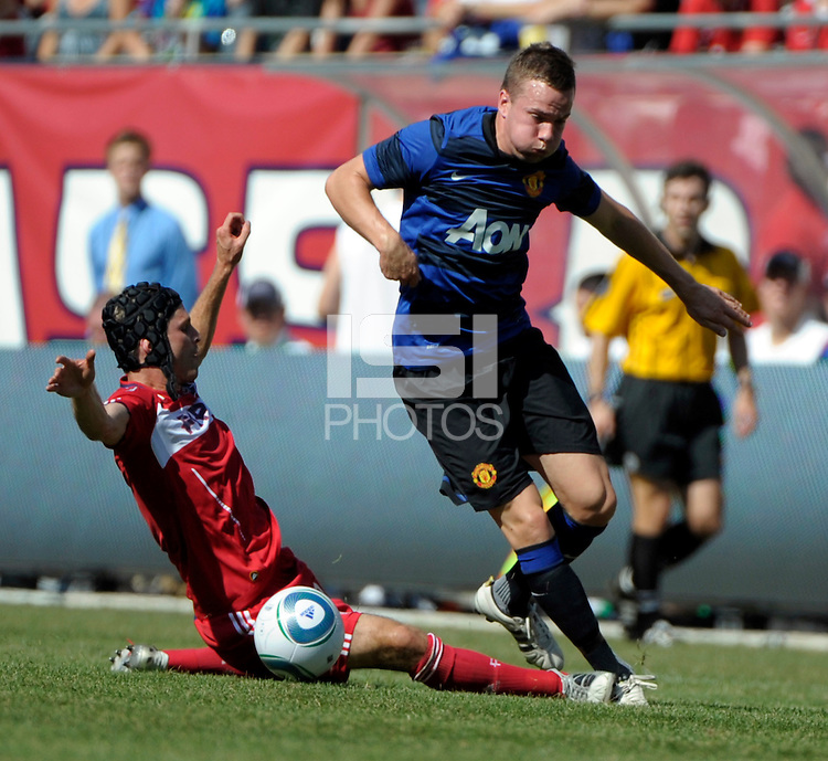 Chicago Fire midfielder Logan Pause (12) fouls Manchester United midfielder Tom Cleverly (35).  Manchester United defeated the Chicago Fire 3-1 at Soldier Field in Chicago, IL on July 23, 2011.