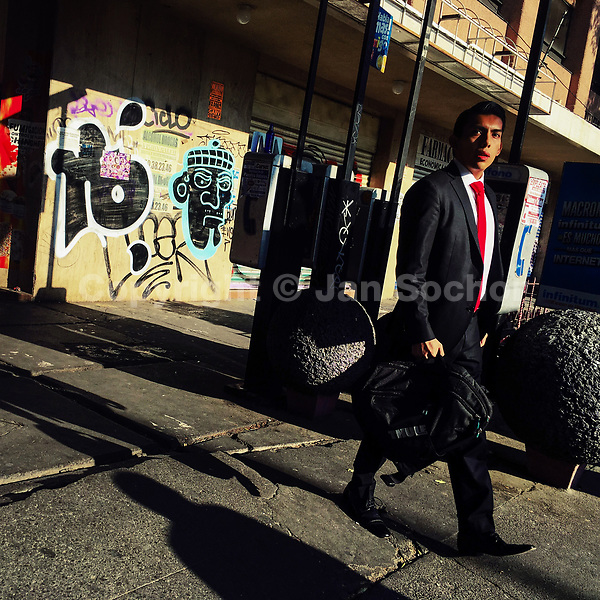 A Mexican office worker walks around the street corner during a sunny morning in Buena Vista neighbourhood, Mexico City, Mexico, 2 April 2018.