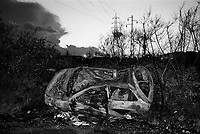 milano, quartiere gallaratese, periferia nord-ovest. una macchina distrutta e data alle fiamme in una strada isolata verso i campi --- milan, gallaratese district, north-west periphery. a wrecked and burnt up car on an isolated road to the fields
