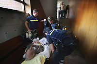 Switzerland. Canton Ticino. Massagno. A senior man lying down on an emergency medical stretcher is being transported from home. The elderly man is suffering from a blood pressure problem and needs to be brought to hospital for a medical examination. Three paramedics check the patient's health in building entrance. The aged man' family looks at the scene from the first floor. The paramedics wear blue uniforms and work for the Croce Verde Lugano. The man and the woman (R) are professional certified nurses, the third (L) is a volunteer specifically trained in emergency rescue. The volunteer carries in his right hand a monitor which controls a set of vital functions, such as  electrocardiogram,  blood pressure's measurement, respiratory rate and pulse oximetry (oxygen saturation), and on his left hand an intravenous infusion with saline solution.The Croce Verde Lugano is a private organization which ensure health safety by addressing different emergencies services and rescue services. Volunteering is generally considered an altruistic activity where an individual provides services for no financial or social gain to benefit another person, group or organization. Volunteering is also renowned for skill development and is often intended to promote goodness or to improve human quality of life. Massagno is a quarter of the city of Lugano. 14.01.2018 © 2018 Didier Ruef