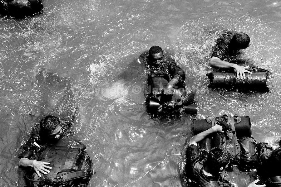 Colombian Police recruits swimm in the water with military kit bags to practise jungle combat tactics, 23 September 2006, Meta ..Department, Colombia.
