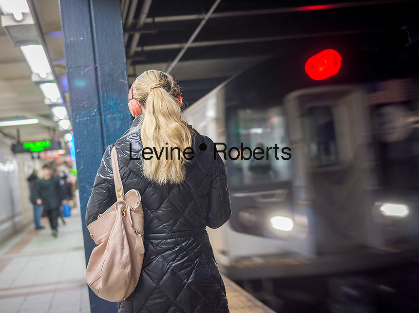 A distracted music listener wears her over the ear headphones as a train arrives at a subway platform in New York on Friday, March 20, 2015. (© Richard B. Levine)