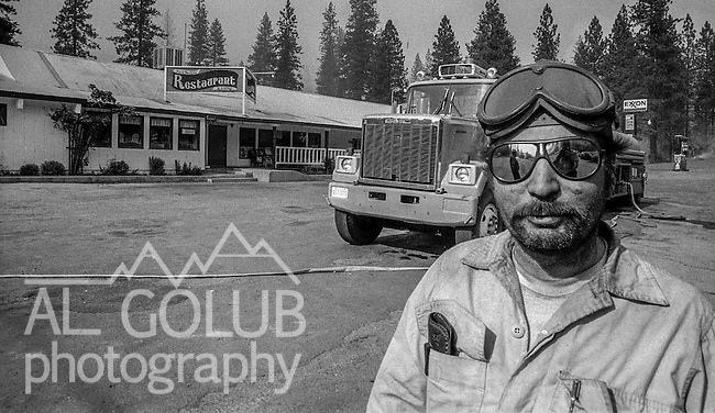 September 3, 1987 Buck Meadows, California –  Stanislaus Complex Fire -- US Forest Service heavy equipment operator maintains water filling station for fire engines at the Buck Meadows Restaurant. The Stanislaus Complex Fire consumed 28 structures and 145,980 acres.  One US Forest Service firefighter, David Ross Erickson, died from a tree-felling accident.