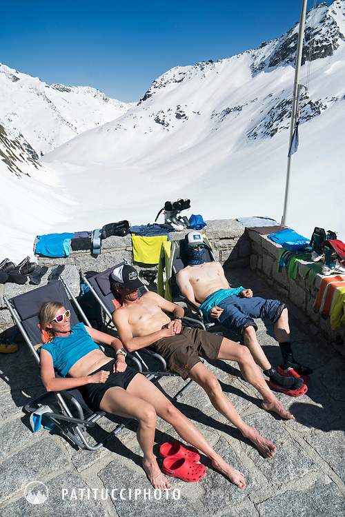 Three ski tourers relaxing in the sun on the Bächlital Hut deck during the Berner Haute Route, Switzerland