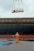Workers at Immingham Docks, on the Humber estuary, unload a shipment of paper pulp from the USA.