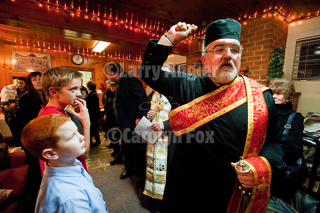 Christmas Eve Vigil Service at St. Sava Serbian Orthodox Church, Jackson, Calif.  Yule Log (badnjak) ceremony. Deacon Triva tosses symbolic walnuts to through the room