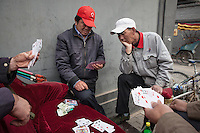 Rickshaw drivers play card at the entrance of one of the surviving Beijing Hutong around Dongsi.