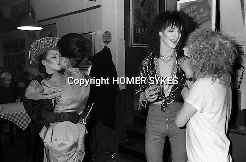 Blitz Kids New Romantics at The Blitz Club Covent Garden, London, England 1980. The couple of girls kissing  Kim Bowen ( wearing a velvet hat by Stephen Jones ) and Julia Fodor (later known as Princess Julia)  and the skinny Jeremy Healy chats with (soon-to-be deejay) Jeffrey Hinton.<br />