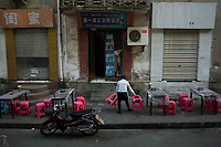Huanggang, Hebei province, China - A waitress sorts out the seatings of an outdoor eatery at the old district of Huanggang,  October 2014. Famous Song dynasty poet and politician Su Dongpo used to live there in exile.