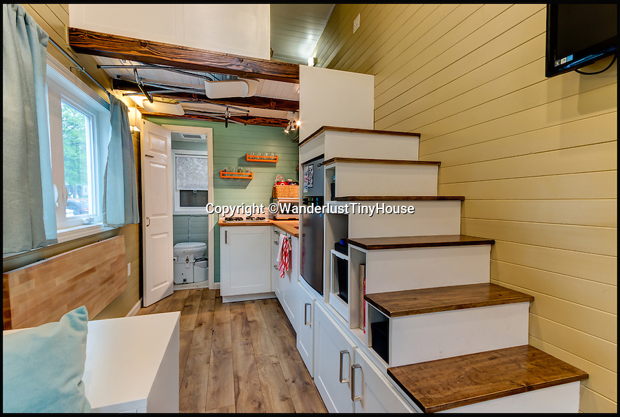BNPS.co.uk (01202 558833)<br /> Pic: WanderlustTinyHouse/BNPS<br /> <br /> Well planned interior is very homely...<br /> <br /> Wanderlust for homebird's -  a young couple have solved the problem of leaving a much loved home to go travelling, by strapping a downsized version to the back of their pick-up and taking it with them.<br /> <br /> Patrick Howard and Lauren Kennedy ditched their office jobs, sold most of their worldly possessions and their 2,000 sq ft home and bought the miniscule 200 sq ft house, which can be towed by a pick-up truck.<br /> <br /> The pair, who were both electrical engineers, are now on their trip of a lifetime travelling all over the United States with their two dogs, Otis and Colbie.<br /> <br /> They are part of the Tiny House Movement - a growing group of people who are buying small houses and enjoying simpler lives.
