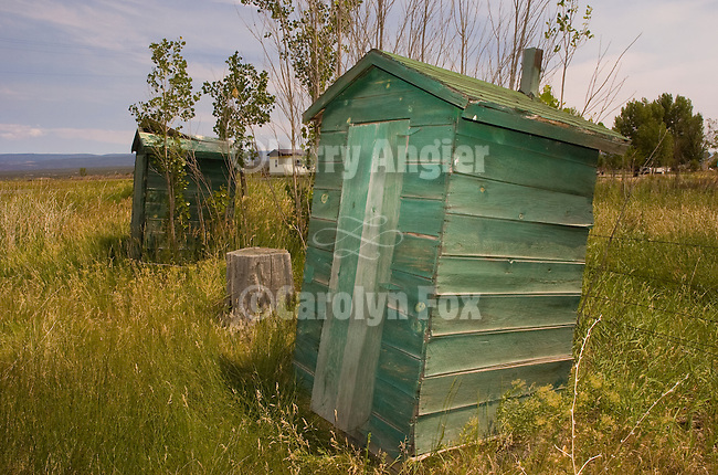 Two leaning wooden green outhouses in southwest Colorado