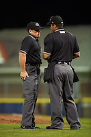 Umpires Greg Roemer and Jose Matamoros discuss a call during a game between the State College Spikes and Batavia Muckdogs August 23, 2015 at Dwyer Stadium in Batavia, New York.  State College defeated Batavia 5-3.  (Mike Janes/Four Seam Images)