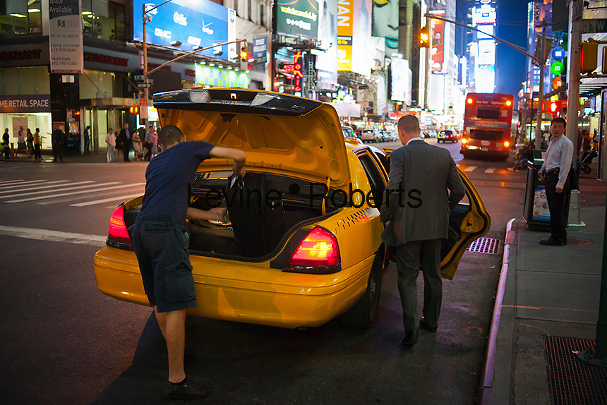 A traveler enters a cab as the cab driver loads his luggage into a taxi in Times Square in New York on Thursday, September 1, 2011   (© Richard B. Levine)