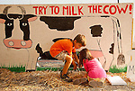Photo by Phil Grout..Sometimes it takes four hands to milk a cow as Garret Cox and Clara Curtis find.out while they practice for the Little Farmer competition at the 4-H Fair at the pretend.cow-milking station..