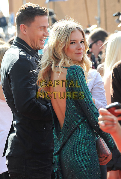 CHANNING TATUM & SIENNA MILLER.The 2009 MTV Movie Awards held at Universal Ampitheatre  in Universal City, California, USA..May 31st, 2009  .half length black suit jacket green backless profile sparkly diamante looking over shoulder.CAP/DVS.©Debbie VanStory/Capital Pictures.