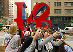 Manhattan, New York, U.S. - May 21, 2014 - Several girl friends take Selfies photos with a cell phone, with the colorful famous LOVE sculpture by Robert Indiana on 6th Avenue in the background, during a pleasant Spring day in Manhattan.