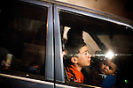 A Guatemalan family drives past a crime scene where police, military, and firefighters investigate a homicide of four drug gangs dealers who were shot and killed, in Zone 10, in Mixco, Guatemala, on Saturday, Nov. 5, 2011. <br />