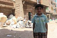 2011 Mokattam Garbage City (alla periferia del Cairo) il quartiere copto dove si vive in mezzo alla spazzatura raccolta: mezzobusto di un bambino in strada tra i palazzi. Dietro di lui un altro bambino con la sua bici accanto a grandi sacchi di rifiuti.