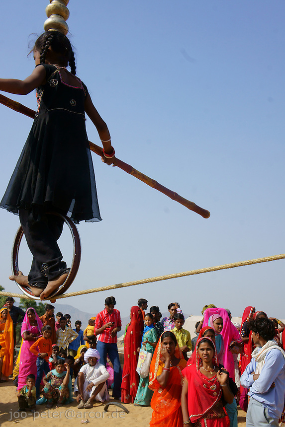 girl acrobat Aarti  showing her art at camel market in holy city Pushkar, Rajastan, India