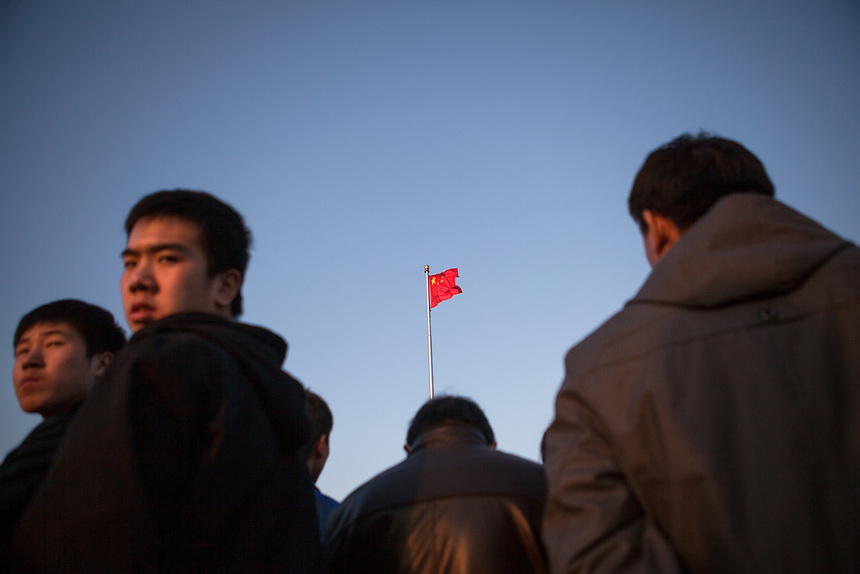 Tourists gather at Tiananmen Square during the flag lowering ceremony.