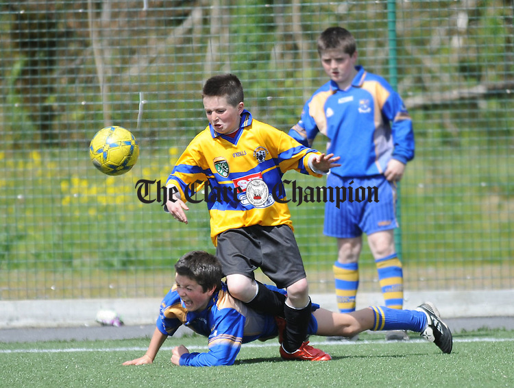 Newmarket's Padraig Mc Mahon falls under the challenge of Liscannor's Brian Considine during the Clare Schools 5 A Sides at Lees Road. Photograph by Declan Monaghan