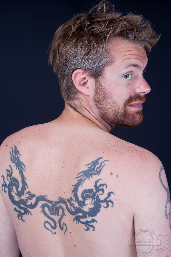 Danish man with tattoos on arms, shoulders, back and legs. On the back is a black, chinese, doubel-headed dragon. On the left shoulder is a band with runes on the right shoulder a biohazard-sign. On the right forarm is a classic triskelion. On the left forarm is a special tattoo. It is a classic dragon on top of a wheel. In the wheel is the text &quot;Sister&quot;. His sister has a circle in her tattoo with the text &quot;Brother&quot;. On his right end left lower leg are identical chinese dragons.<br /> All tattos except the dragon on the left arm are are done at Miss Roxy tatoo studio. The dragon is done by Fine Line Tattoo