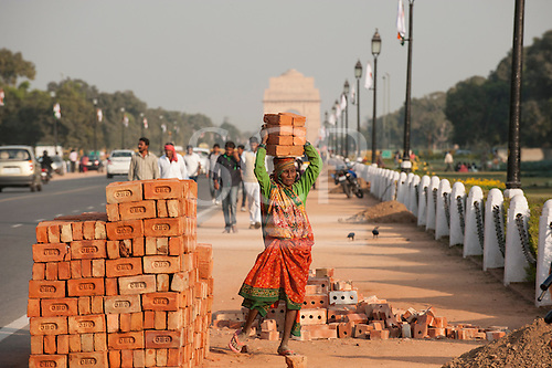 Delhi, India. A woman labourer carrying 8  eight bricks on her head from a pile of bricks at the side of the road near the India Gate.