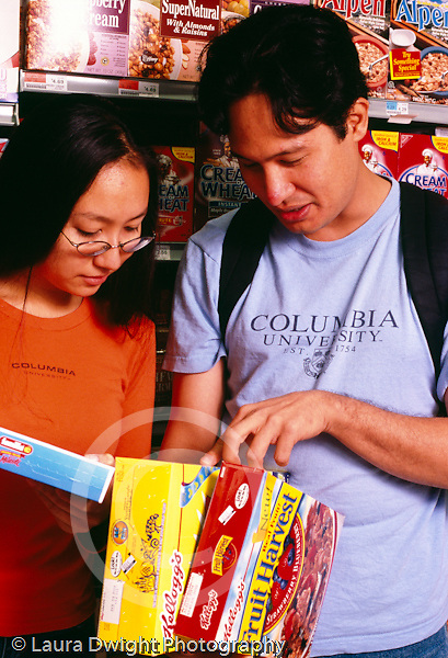 College student female shopping at supermarket, in cereal section reading labels w. male friend