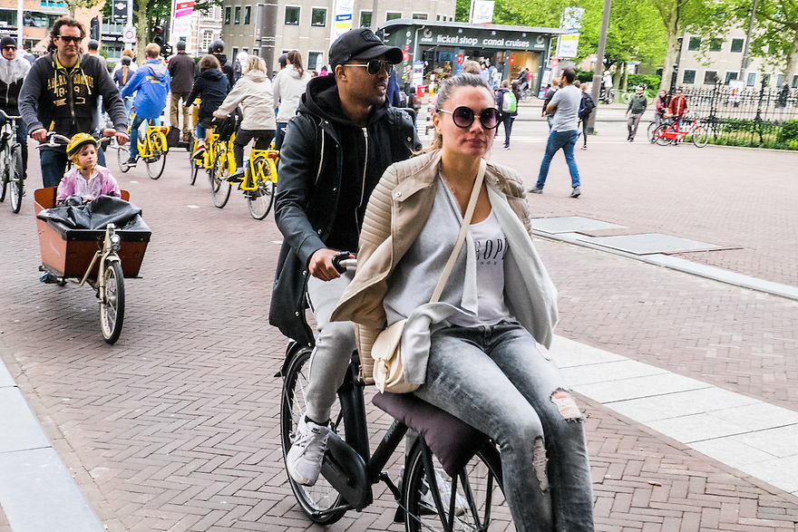 Nederland, Amsterdam, 30 mei 2015<br /> Fietsverkeer in de stad. Er zijn veel verschillende manieren om nog een passagier mee te nemen op de fiets. Tegenwoordig hebben veel fietsen ook een bagagedrager voor op de fiets. Daar kan je natuurlijk ook heel goed je meisje op veroeren. <br /> Foto: Michiel Wijnbergh