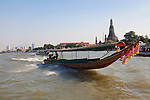Traveling by boat down the Chao Phraya River through downtown Bangkok, Thailand,
