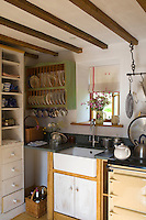 A green-painted plate rack hangs on the wall adjacent to the butler's sink in this compact country kitchen