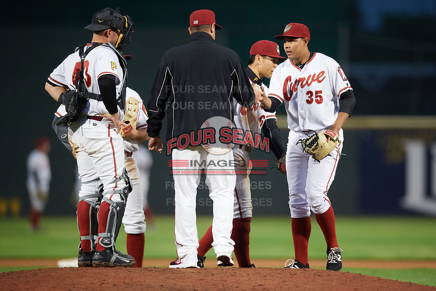 Altoona Curve relief pitcher Miguel Rosario (35) takes the ball from manager Michael Ryan (12) for a pitching change as catcher Jackson Williams (43) looks on, Connor Joe taps Rosario on the leg, during a game against the New Hampshire Fisher Cats on May 11, 2017 at Peoples Natural Gas Field in Altoona, Pennsylvania.  Altoona defeated New Hampshire 4-3.  (Mike Janes/Four Seam Images)