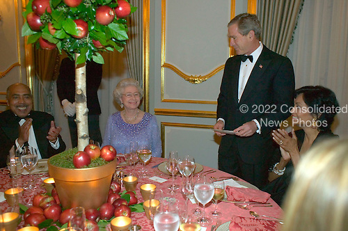 United States President George W. Bush toasts Her Majesty Queen Elizabeth during a thank-you dinner at Winfield House, the U. S. Ambassador's residence, in London Thursday, November 20, 2003. Sitting with Her Majesty and The President are Dr. Walter Massey, President of Morehouse College in Georgia, left, and Lady Shakira Caine, wife of actor Michael Caine. Not pictured are Laura Bush, Prince Philip, Duke of Edinburgh, and Prince Charles. The President and Mrs. Bush were in the United Kingdom for an official State Visit.