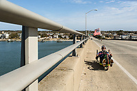 Morehead City, NC -- Quadriplegic hand cyclist Paul Kelly, 62, climbs the bridge to Atlantic Beach over the intercostal waterway on a training ride for the Boston Marathon. The strenuous climb can take 10 minutes. Tuesday, March 27, 2018. (Justin Cook for The Wall Street Journal)<br /> <br /> SUMMARY:<br /> <br /> Paul Kelly, hand cyclist, Beaufort, NC Training for the Boston Marathon so we would want to shoot in March to run the week before the marathon or marathon Monday, Apriln16. Life as a quadriplegic doesn&rsquo;t keep 62-year-old Paul Kelly on the sidelines. After breaking his neck in a swimming accident in 1978, Kelly was determined to find fitness activities to maintain an active lifestyle. He discovered handcycles while watching his niece compete in the 2006 Marine Corps Marathon and was inspired to start his own marathon career to stay fit. Paul has competed in over 100 half and full marathons. On April 16, he will celebrate his 40th year of living as a quadriplegic by taking on one of the most coveted races for a marathoner -- the Boston Marathon. Kelly is among the 60 handcyclists competing in the 2018 Boston Marathon with a qualifying time of 1:26:37. Most of Paul&rsquo;s distance training takes place at Bogue Banks, which includes Atlantic Beach, Salter Path, and Emerald Isle, N.C. It&rsquo;s Nicholas Sparks worthy scenery with its marshes, waterways, inlets and small islands. Paul is particularly fond of the approach from Atlantic Beach to Bogue Banks -- it&rsquo;s via the high-rise bridge. In cold weather, Paul has to be mindful of the environment and dress in a manner that insulates his legs while also allowing his upper body to ventilate. Paul chooses to train at times of day when the temperatures are more reasonable. He uses hand warmers in his gloves, on the inside the grips on his handcycle and in the legs of his trousers.