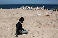 An illegal African migrant is pictured downcast on the Tajoura shore after having been arrested from the Mediterranean Sea by the Libyan coastguard in the west of Libya.