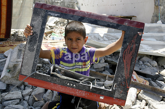 "A Palestinian boy holds a damaged television on the rubble of a destroyed house in Khan Yunis in the southern Gaza Strip on September 11, 2014. Israel's deputy foreign minister,Tzahi Hanegbi , warned that Hamas was likely to resume ""violence"" if it feels it has made no political gains from upcoming talks in Cairo. Photo by Abed Rahim Khatib"
