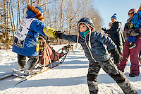 Young Ayden Tuttle gives a high-five to Mellisa Stewart on the bike/ski trail during the Ceremonial Start of the 2017 Iditarod in Anchorage on Saturday March 4, 2017 <br /> <br /> Photo by Jeff Schultz/SchultzPhoto.com  (C) 2017  ALL RIGHTS RESVERVED
