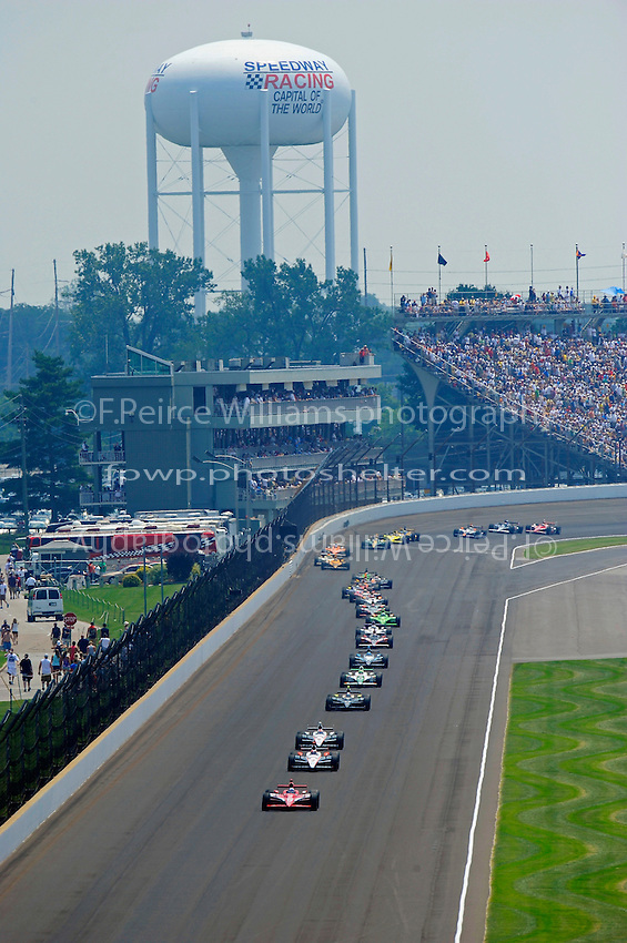 Scott Dixon (#9) leads a pack of cars up the back straight.