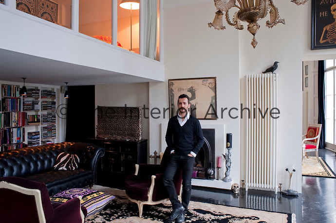 Fashion designer Kinder Aggugini in the spacious living room of his London apartment