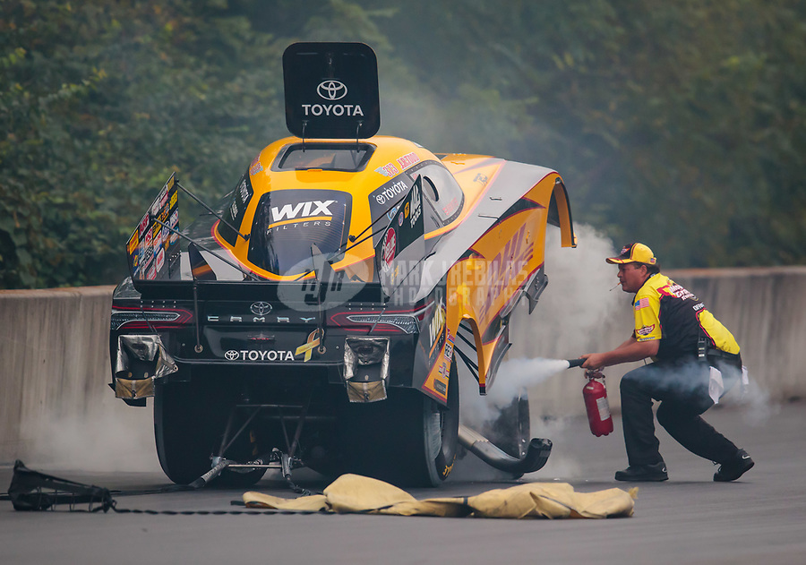 Sep 14, 2018; Mohnton, PA, USA; A safety crew member with a cigarette in his mouth uses a fire extinguisher to put out an engine fire on the car of NHRA funny car driver J.R. Todd during qualifying for the Dodge Nationals at Maple Grove Raceway. Mandatory Credit: Mark J. Rebilas-USA TODAY Sports