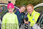 Garda Jonathan McCarthy showing Teresa-Marie O'Shea & Ciara O'Sullivan how to work the speed gun at the Dolly and Teddy walk in The Glen on Saturday.