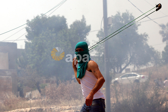 A Palestinian protester uses a sling-shot to hurl stones toward Israeli soldiers during a protest against the expropriation of Palestinian land to expand the Jewish settlement of Halmish, in the West Bank village of Nabi Saleh, on May 27, 2011. Photo by Issam Rimawi