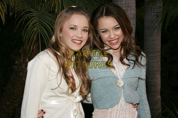 "EMILY OSMENT & MILEY CYRUS.At the press junket for the Disney Channel's ""Hannah Montana"" at the Ritz Carlton Huntington Hotel in Pasadena, CA.  .January 10th, 2006.Photo: William Scott/AdMedia/Capital Pictures.Ref: WS/ADM.half length white blue cardigan.www.capitalpictures.com.sales@capitalpictures.com.© Capital Pictures."