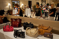 "Newport, California, July 22, 2011 - Women peruse the designer handbags at The Divorcee Sale at the Pelican Hill Resort in Orange County. Organized by Jill Alexander, the sale offers luxury items most of which from uber-rich divorcees looking to unload their proverbial baggage. The event also donates 25 percent of its profits to breast cancer research...Alexander, who has actually never been married, started The Divorcee Sale this past spring after noticing a trend amongst her friends and colleagues going through divorces. ""Many women have an attachment to these things and they just want to move on,"" says Alexander. She added that the consignment shops were full and not really offering much in the way of sympathy in the situation. Alexander is different in that she visits the home of the divorcees, often with cakes and tissues, and acts as both a consignor and a confidant. ."
